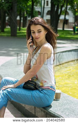 a charming young woman sitting on the street and talking on the phone