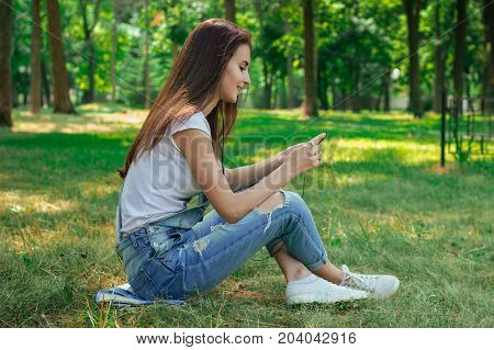 smiling charming girl sits in the Park on the grass and looking at the phone