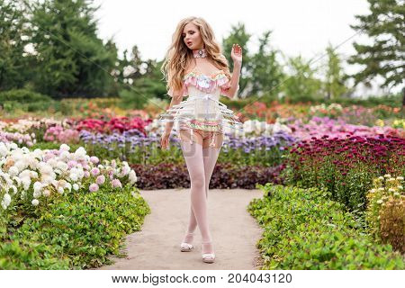 Sexy blonde woman wearing beautiful lingerie with stockings and corset, walking in blooming garden. Hot female in underware posing in sensual way outdoors. Female fashion, model fitted like a doll, barbie