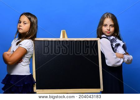 Schoolgirls Next To Chalkboard Isolated On Blue Background
