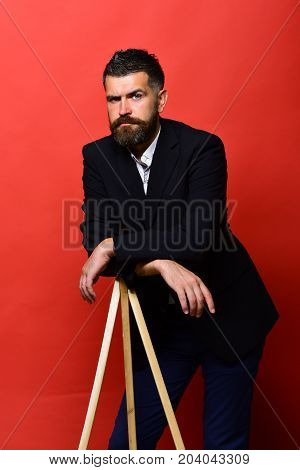 Macho Man Leans On Tripod On Red Background