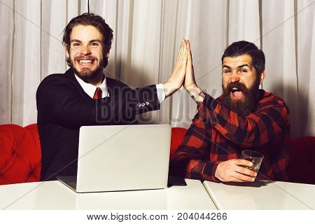 bearded men businessmen long beard brutal caucasian hipster with moustache hold glass with whiskey has smiling happy face unshaven guys with stylish hair in suit and red tie with laptop