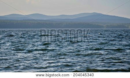 view on the opposite shore of the misty lake, the distance the Ural mountains, South Ural, Uvildy