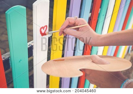 Close up of female hand holding paint brush and drawing red heart shape on colorful wooden fence outdoor. Love and art concepts.