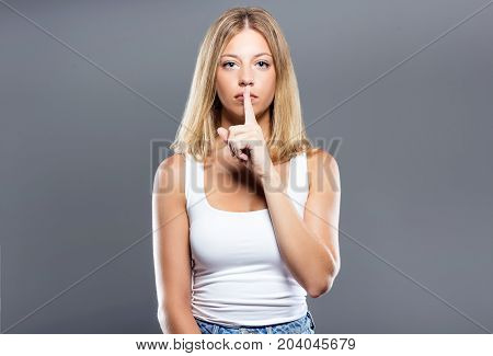 Beautiful Young Woman Asking To Keep Quiet Over Gray Background.