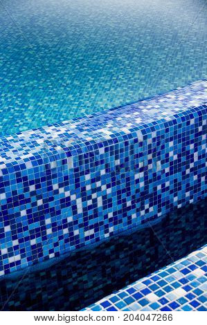 close-up edges of the swimming pool with blue mosaic tiles