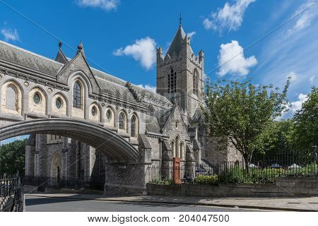 Dublin Ireland - August 7 2017: Gray stone Christ Church Cathedral with overpass link to Dublinia building against blue sky with white clouds. Green vegetation. Art market in back.