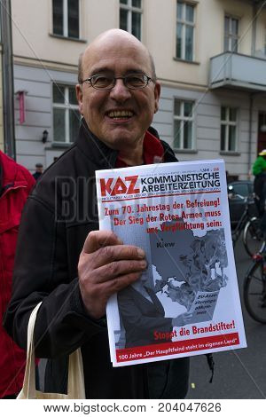 BERLIN - MAY 01 2015: International Labour Day. Distributor of Communist newspapers.