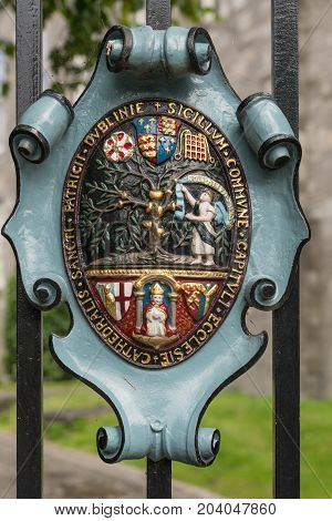 Dublin Ireland - August 7 2017: Metal shield fixed on black fence shows colorful Coat of Arms of Saint Patrick Cathedral.