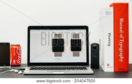 PARIS FRANCE - SEP 13 2017: Minimalist creative room table with Safari Browser open on MacBook Pro laptop at Apple Computers website with latest Apple Watch Series 3 with selction of apple watc face band
