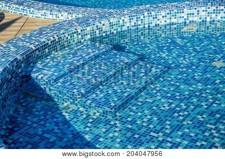 close-up steps to the swimming pool with blue mosaic tiles