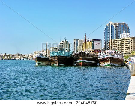 Dubai, United Arab Emirates - July 5, 2004: Traditional wooden boats, called Dhow, are moored on the banks of the Creek in Dubai.