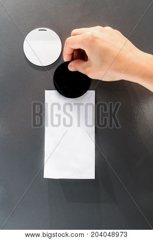 Woman Hand Pasting Black Magnet And White Paper On Grey Metal Board