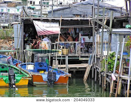 Tai O, Hong Kong - March 24, 2003: Some people are sitting in a house in the fishing village Tai O, built on stilts above the water.