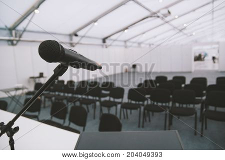 Black microphone in conference room - empty chairs on background, wide angle