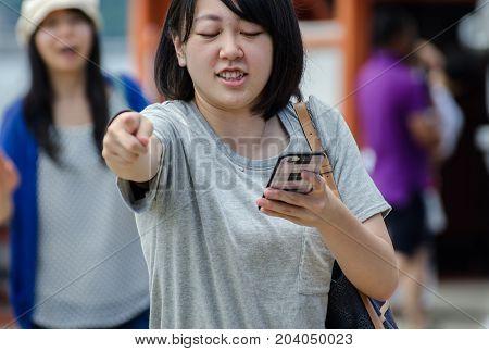 Japanese Woman Pointing For Direction During Walking At Miyajima (itsukushima ) Island. Japan