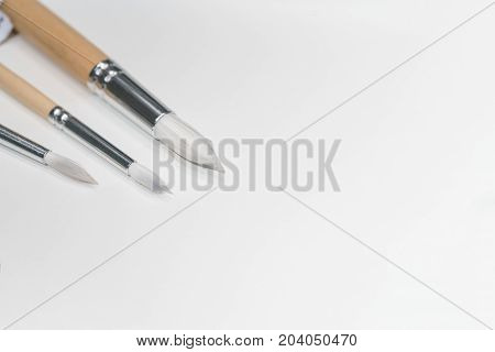 Three different white paint brushes on cork board background with copy space