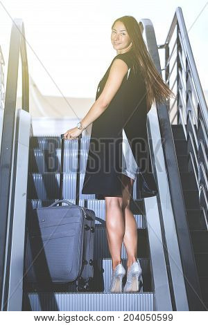 Confident Woman With Suitcase On Escalator