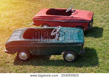 Green and red vintage toy cars on a green grass field. Side view. Sunset light