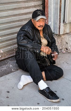 Homeless Man Sitting Outside With A Cigarette