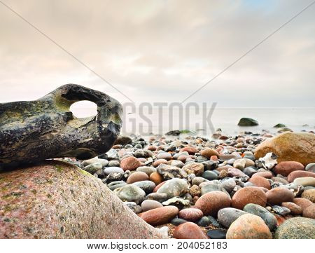 Bizzare Stones On Costline, The Stony Beach Ends In Smooth Water Of Blurred Ocean.