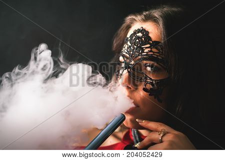Closeup Young, beautiful girl smoke a hookah at club. Sexy woman smoking. Fashion