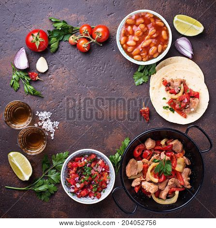 Concept of Mexican food.  Salsa, tortilla, beans, fajitas and tequila Top view