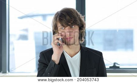 Businessman Answering Call At Work On Smartphone