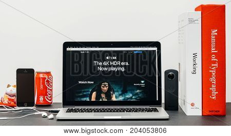 PARIS FRANCE - SEP 13 2017: Minimalist creative room table with Safari Browser open on MacBook Pro laptop showcasing Apple Computers website with latest Apple TV 4k with the 4k era now playing