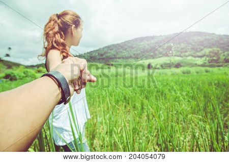 Lover women and men asians travel relax in the holiday. Lovers walk hand in hand on grassland.