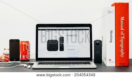PARIS FRANCE - SEP 13 2017: Minimalist creative room table with Safari Browser open on MacPook Pro laptop showcasing Apple Computers website with latest Apple TV 4k with storage option and price