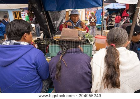 February 27 2017 Otavalo Ecuador: indigenous people stiing at a food stand in the Staurday farmers market