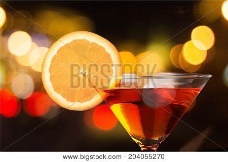 Glass orange slice martini color background party