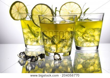 Three Yellow Cocktails With Lemon And Rosemary Standing On Glass In Studio