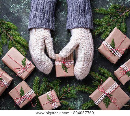 Hands in mittens holding a Christmas gift box. Selective focus