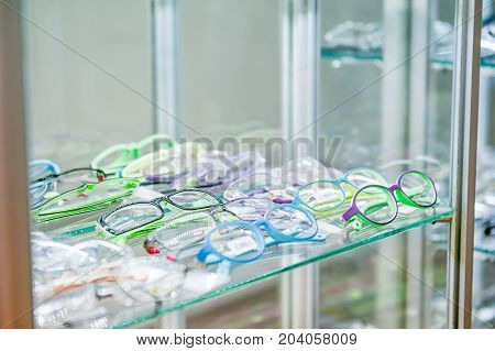 Various of eye glasses on the shelf in the optic shop. Selective focus. Space for text.