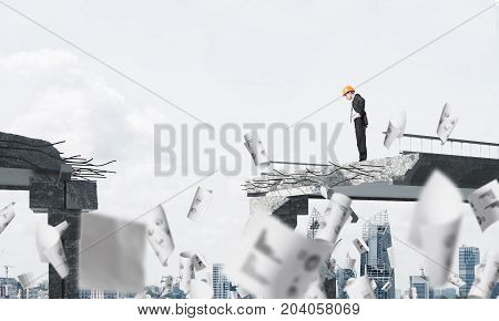 Young engineer in suit and helmet looking down while standing among flying papers on broken bridge with cityscape on background. 3D rendering.