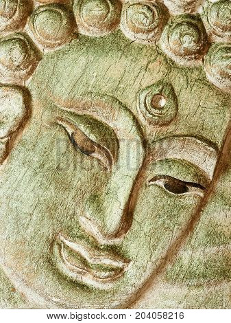 Buddha's face on a wooden board, close up. Wooden relief.