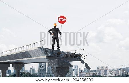 Rear view of engineer in helmet holding stop sign while standing on broken bridge with cityscape on background. 3D rendering.
