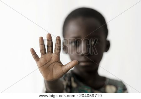 African boy makes a STOP sign with his hand, isolated on white