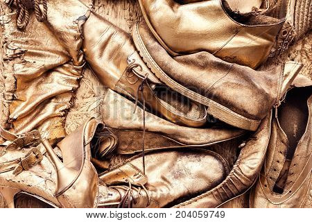 Bunch of old worn out shoes and boots painted in golden yellow color