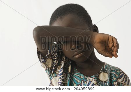 African boy holding his arm in front of his face, as a racism beating sadness symbol, isolated on white