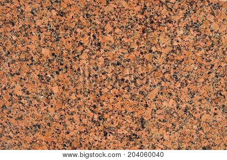 Facing material red granite texture. Natural stone red granite background texture. Bright hard red granite rock texture. Red granite stone background texture. Red granite untreated surface. Facing material full frame horizontal red granite texture.