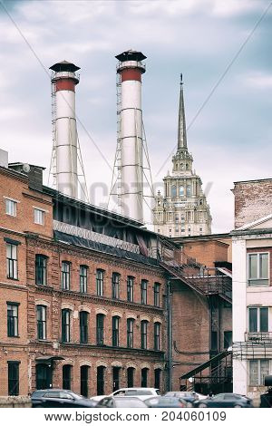 Mix of two pipes and buildings of different times against blue sky. Old Industrial building of the factory from red brick, smoking chimneys, tower residential building