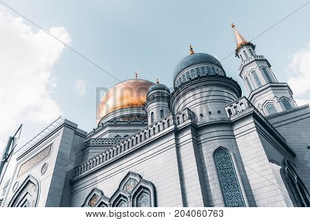 View from bottom side of beautiful Grand Cathedral Mosque made of stone: golden dome and spires with quotation from Quran sunny autumn day Moscow Russia