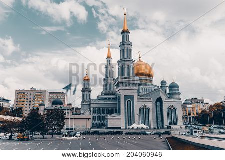 Frontal view of The Grand Cathedral Mosque: bright golden domes and spires with crescents ornamental facade residential houses around parking with cars in foreground Moscow Russia