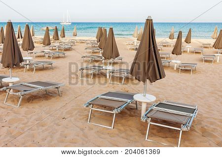 Empty beach loungers and closed parasols with ocean and lonely yacht in the background