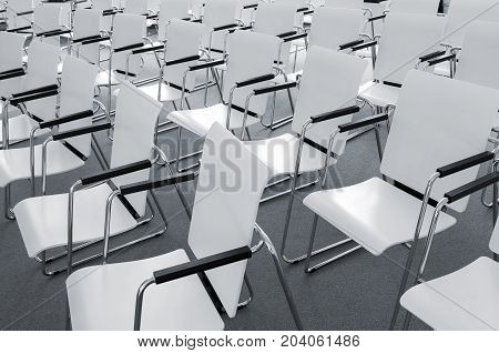 Rows of empty white modern chairs in a conference room
