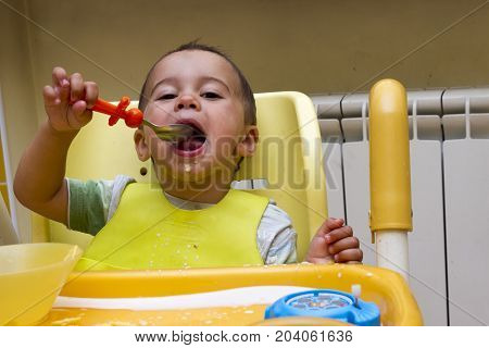 Little boy sits in a children's chair and studies have meals. The first independent actions of the child.