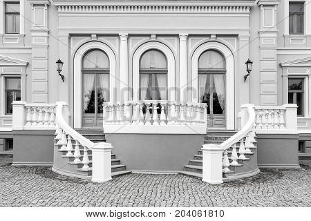 Exterior detail of an old neo renaissance building with stairs and windows black and white picture